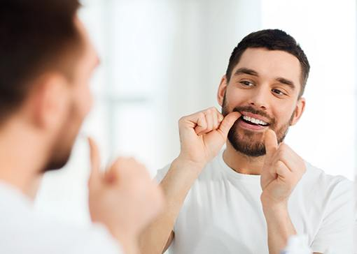 Man flossing teeth after receiving dental crown restoration
