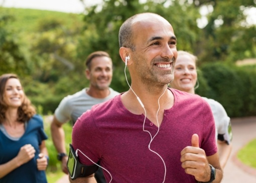 Man with dental implant replacement tooth smiling and jogging with friends