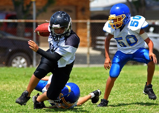Young athletes playing football with athletic mouthguards