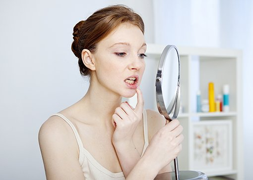 Woman looking at smile in mirror during smile makeover consultation