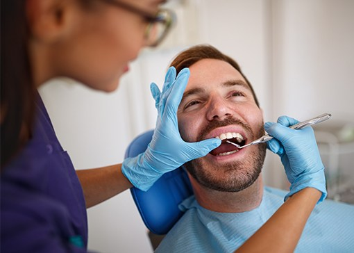 Dental team member examining patient's smile during tooth preparation
