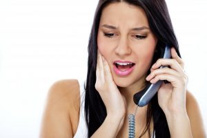 woman experiencing jaw pain calling an emergency dentist